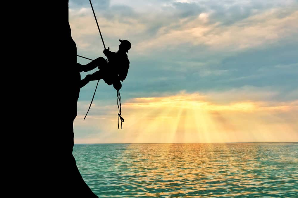 Man climbing cliff over the ocean